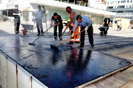 Beim Verteilen der 220 Grad Celsius heißen ersten Asphaltschicht geraten die Arbeiter auch bei kühleren Temperaturen auf der Siegbrücke ins Schwitzen. (Foto: Stadt)