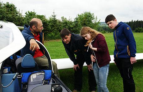 """Bevor es in die Luft gehen konnte, gab es am Flugzeug eine technische Einweisung. Segelflugreferent Enrico Busch-Hecht (links) und sein Kollege Uwe de Fries begleiteten die Novizen anschließend bei ihren ersten """"Gehversuchen"""" hoch am Himmel. Foto: LSG"""