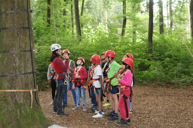 Nicht nur die Leistung des Einzelnen, sondern die Hilfe der ganzen Gruppe ist im Kletterwald gefragt. Die Hoodies-Erlebnispädagogin Katja Seliger erklärt den jungen Teilnehmern, was es zu beachten gilt. (Fotos: Gemeinde Neunkirchen)