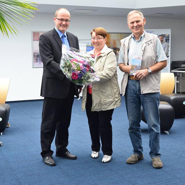 Filialleiter Thorsten Seiler überreicht den Blumengruß an Angela Schmitt. Ihr Mann Heinrich freut sich über den Reisegutschein. (Foto: Volksbank)
