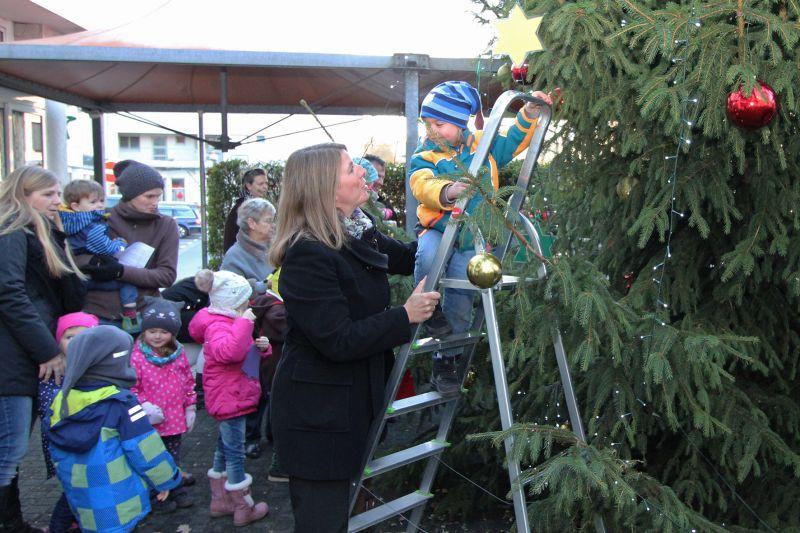 """Wilnsdorfs Bürgermeisterin leistete Sicherungsarbeit, während ein Knirps aus dem """"Spatzennest"""" den Wilnsdorfer Weihnachtsbaum dekorierte. (Foto: Gemeinde Wilnsdorf)"""