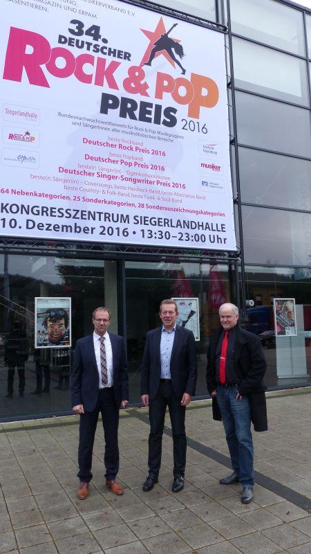 Markus Schäfer von der Volksbank Siegerland, Bürgermeister Steffen Mues und Friedrich Schmidt, Hallendirektor der Siegerlandhalle freuen sich, dass der Deutsche Rock- und Pop-Preis nun schon zum dritten Mal in Folge in Siegen stattfindet (v.l.). (Foto: Stadt Siegen)