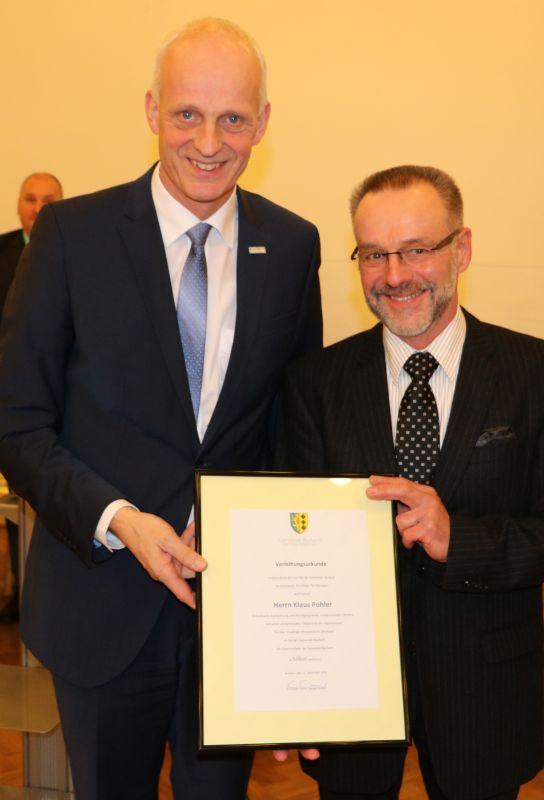 Für die 10-jährige Mitgliedschaft im Rat der Gemeinde Burbach erhielt Klaus Pohler die Ehrenmedaille in Silber nebst Urkunde von Bürgermeister Christoph Ewers überreicht. (Foto: Gemeinde Burbach)