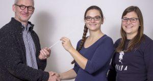 1. Vorsitzender Reiner Klinge (links) und 2. Vorsitzende Lorena Käuser (rechts) übergeben den Taktstock an die neue Dirigentin Simone Schlesak (mitte). (Foto: Musikzug Netphen)