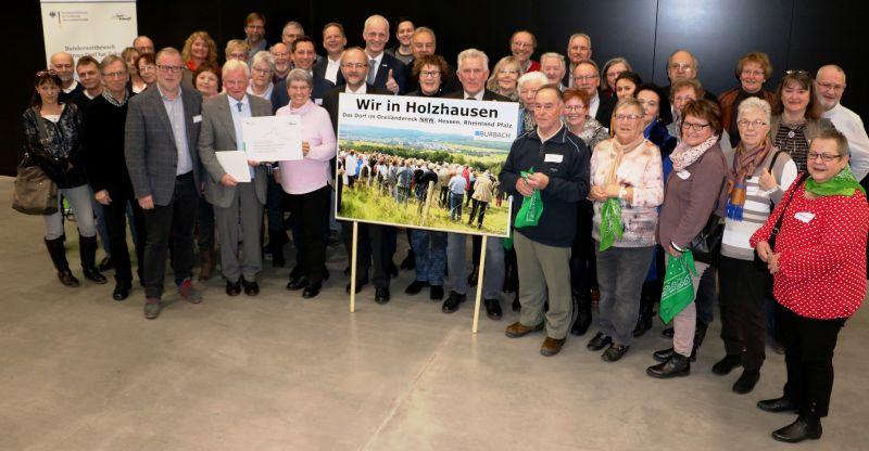 Bundeslandwirtschaftsminister Christian Schmidt überreicht die Auszeichnungsurkunde an die Vertreter der Dorfgemeinschaft Holzhausen.